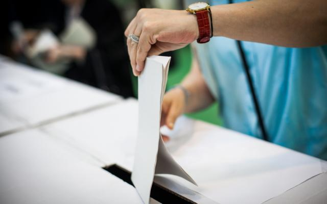 Hand of a person casting a ballot at a polling station during voting